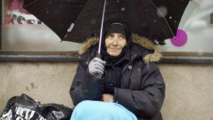 Bella tigger på gatorna i Borås under ett paraply.
