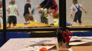 Saxar på ett bord i fokus. I bakgrunden ser vi små pojkar som hoppar och leker på en madrass.