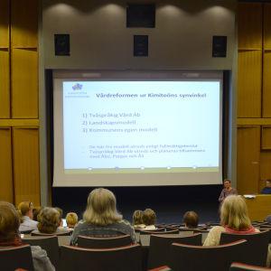 Auditorium med människor fotade bakifrån.