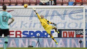 Wigan-målvakten Jussi Jääskeläinen räddar Derby-spelaren Derby Johnsons skott.