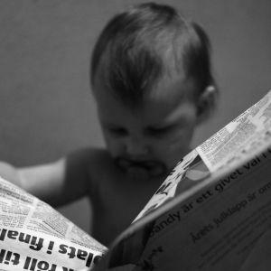 Barn läser tidning. Bilden är svartvit.