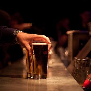 En hand sträcker sig efter ett ölstop på en bardisk.