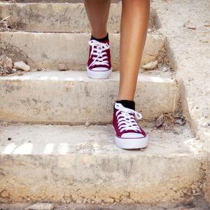En person med bara ben och röda skor går i en trappa.
