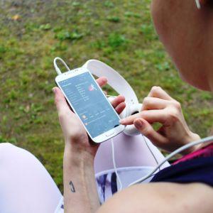 Tyttö lähdössä juoksulenkille puhelimen kanssa.