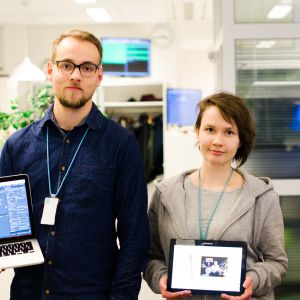 Två personer håller upp apparater med barninnehåll