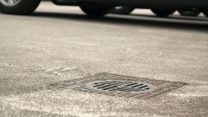 Sadevesikaivon kansi pihakannella, jossa on pysäköintialue. Taustalla autoja.