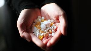 Erilaisia lääkkeitä kourassa.