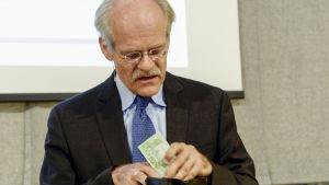 Stefan Ingves drar upp 200 kronor ur sin plånbok.