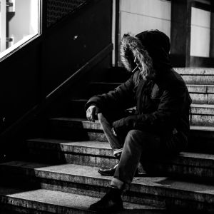 Ung man med jacka och huva på sitter ute på en trappa och röker