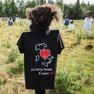 Hiljainen kansa -teoksen heinäseiväshahmo, jolla musta t-paita, jossa italiankielinen teksti La terra trema, il cuore no.