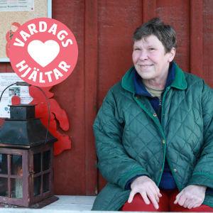En kvinna sitter på en bänk brdvid en lykta och en tomte.
