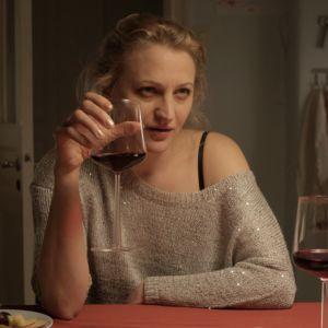 Exfrun sitter vid ett köksbord med ett rödvinsglas i handen.