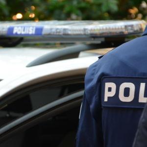 Polis framför polisbil.