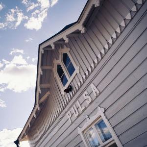 Vaalean vanhan puisen rautatieaseman pääty, teksti Pulsa, taustalla taivasta ja pilviä