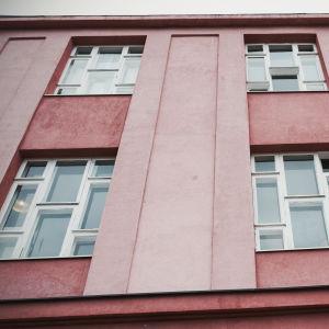 Vanha kerrostalo, kahdeksan ikkunaruutua joka ikkunassa, julkisivu vaaleanpunainen.