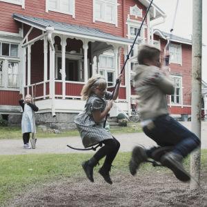 Barn snurrar i rep runt en stolpe.