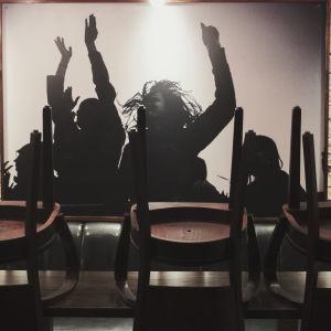 Ravintolapöytä jolla pinottuja tuoleja, taustalla iso valokuva ihmisistä jotka tanssivat kädet taivasta kohti.