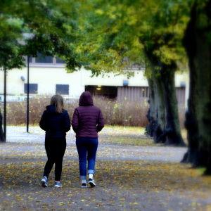 Ungdomar går i en park.