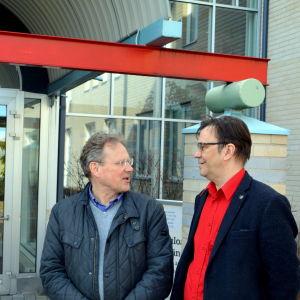 Två män står utanför skolentré.