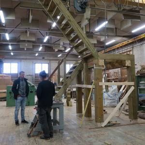 Två personer intill ett halvfärdigt utkikstorn inne i en träverkstad.
