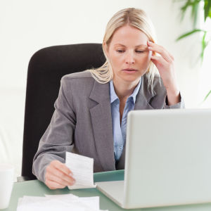 Kvinna sitter bakom en bärbar dator. Hon ser bekymrad ut och ser på en lapp som hon har i handen.