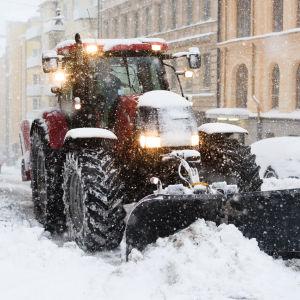 En traktor röjer snö på en trottoar.