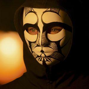En flicka med en svart luvtröja har en svartvit mask över ansiktet och håller i en brinnande fackla.