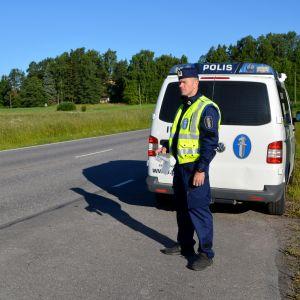 Kommissarie Freddie Cederlund övervakar trafiken med ett blåstest i handen.