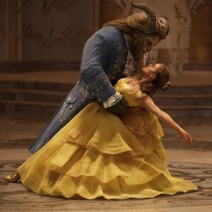 Skönheten Belle dansar i gul klänning tillsammans med Odjuret.