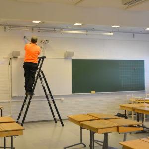 En man i orange tröja står på en stege och lägger tätning vid taklisten i ett klassrum.