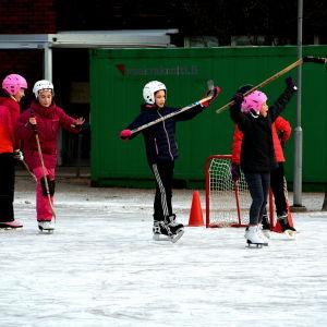 Skolelever spelar sihockey och hurrar.