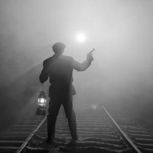 Pojke står med en stormlykta och en pistol och stannar ett annalkande tåg. Iscensatt bild för dokumentären.