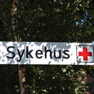 En vägskylt där det står sykehus, det vill säga sjukhus på norska.