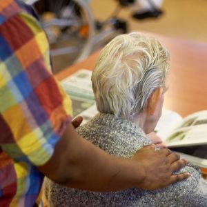 Ung man masserar äldre mans axlar.