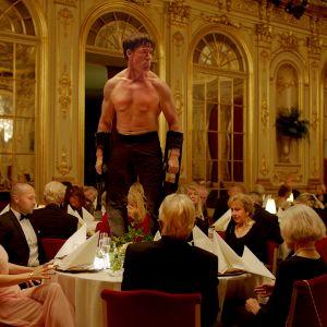 Storvuxen man utan skjorta står på ett middagsbord, de finklädda gästerna är förfärade.