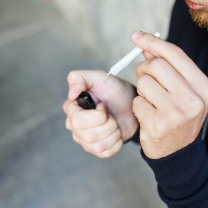 Närbild på en anonym man som håller på att tända en joint.