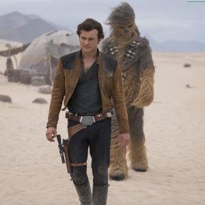 Han Solo (Alden Ehrenreich) och Chewbacca (Joonas Suotamo) går igenom ett sandlandskap.