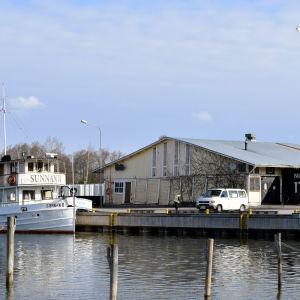 En vy över Norra hamnen i Ekenäs. Till vänster syns fartyget Sunnan och i mitten det gamla gula hamnmagasinet.