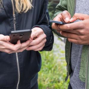 Två unga personer med mobiltelefoner.