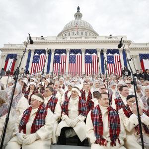 En kör sitter utanför Capitol iförda regn- och andra varma kläder och väntar på att ceremonin där Donald Trump svär presidenteden ska börja.