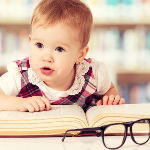 Ett litet barn hänger över en stor bok.