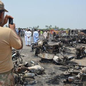 En pakistansk soldat fotograferar olycksplatsen i utkanterna av Bahawalpur, Pakistan 25.6.2017