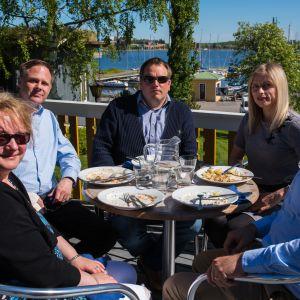 fem personer äter lunch på uteservering