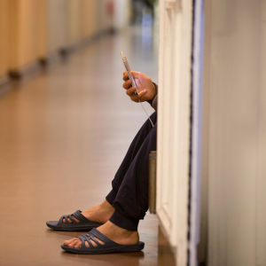 En flykting sitter på golvet med sin mobil i handen.