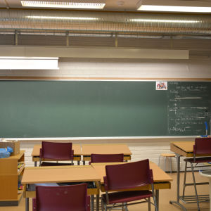 Ett klassrum med pulpeter och anteckningstavla