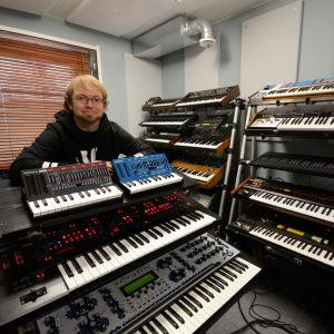 Artisten Kebu i sin studio omgiven av analoga syntar.