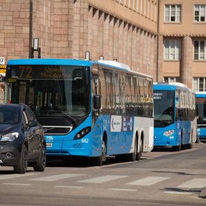 Busseja ja henkilöautoja jonossa rautatieaseman liikennevaloissa Helsingissä.