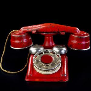 En röd telefon med roterande nummerbricka.