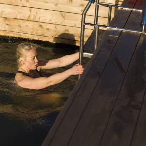 Jessica Wolff på väg upp ur vattnet. Hon håller i en stege som är fast i en kaj. Hon ser ut att frysa.