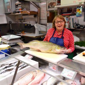 Liana Miettinen håller upp en gös i fiskdisken.